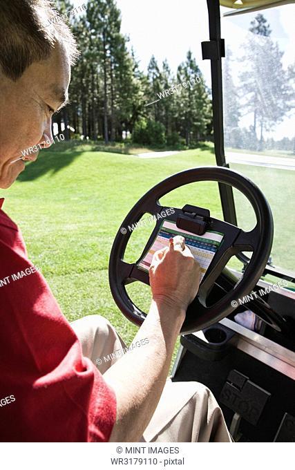 Senior golfer recording his score on a score card in a golf cart
