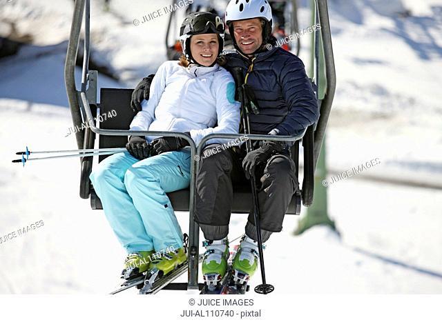 Couple riding on ski lift at resort