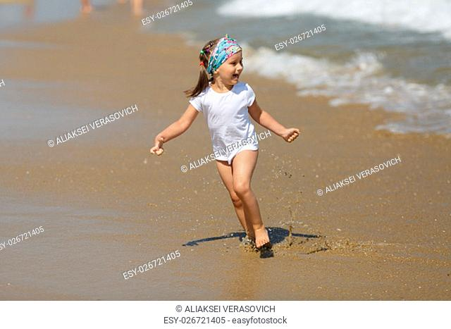 Smiling child in a white t-shirt runs the water's edge on the beach on a clear sunny day. Shallow depth of field. Focus on the model