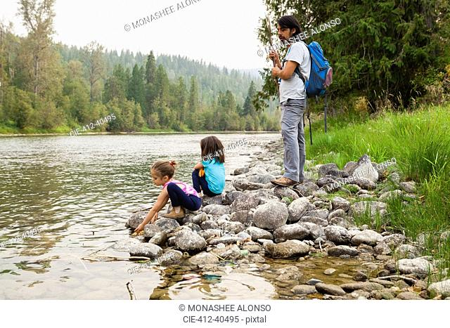 Father and daughters hiking, resting at lakeside