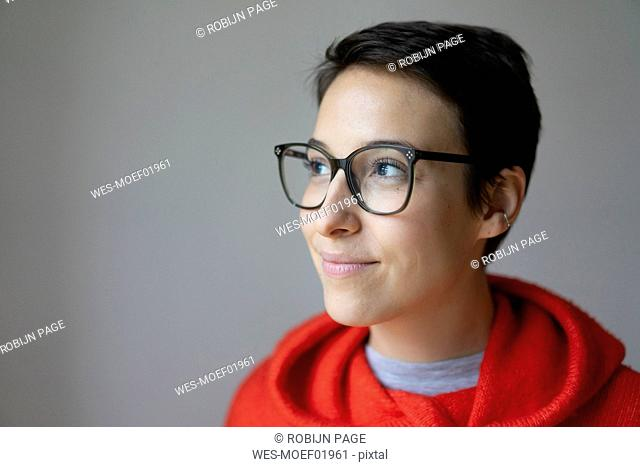 Portrait of a smiling young woman with short hair, wearing glasses