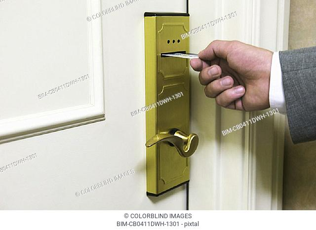 Businessman's hand unlocking hotel room door