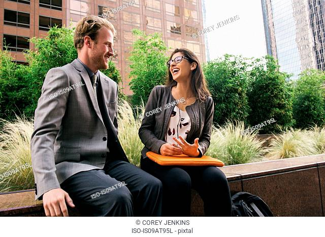 Businessman and woman in city sitting on wall talking