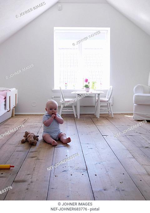 Baby girl sitting on wooden floor, Sweden