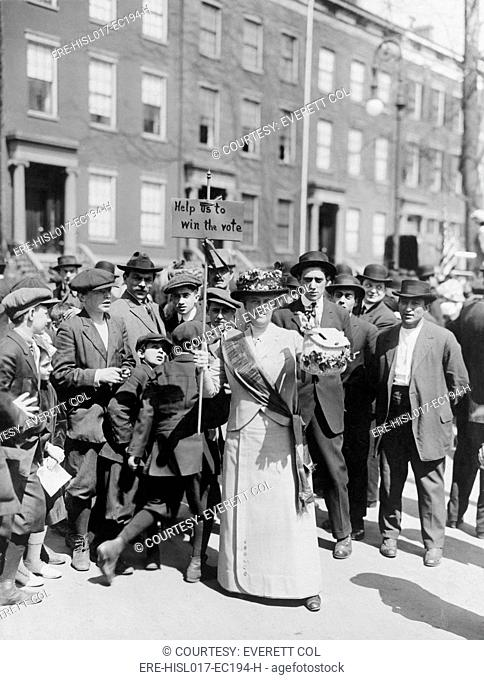 Women identified as Mrs. Suffern, is surrounded by a crowd of men and boys, while she holds a home-made banner in women suffragist parade 'Help us to win the...