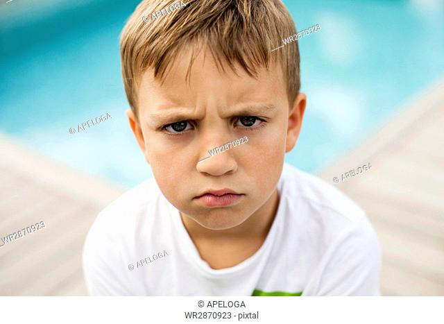 Portrait of angry boy against swimming pool