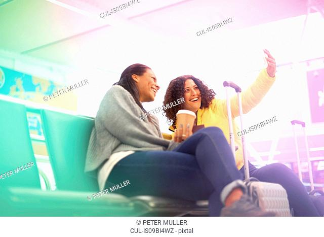 Two mid adult women taking selfie in airport departure lounge