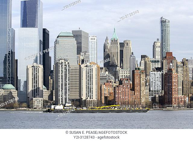A barge on the Hudson River passes by Manhattan, New York City
