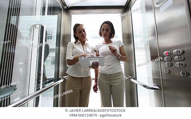 Two executive elevator up and using digital tablet , Office building, Business, San Sebastian Technology Park, Donostia, San Sebastian, Gipuzkoa, Basque Country