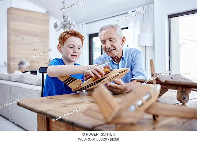 Grandfather and grandson building up model airplanes