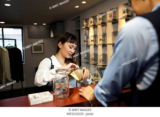 Smiling Japanese woman standing at counter in clothing store, paying with credit card