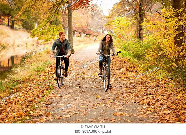 Happy young couple cycling on riverside in autumn