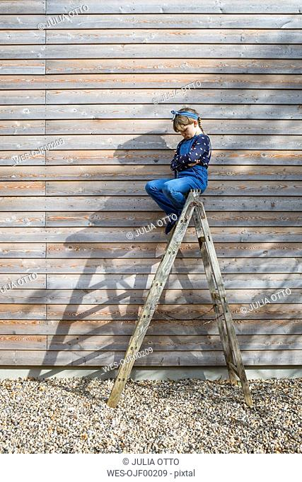 Girl sitting on ladder in front of a wooden facade pouting mouth