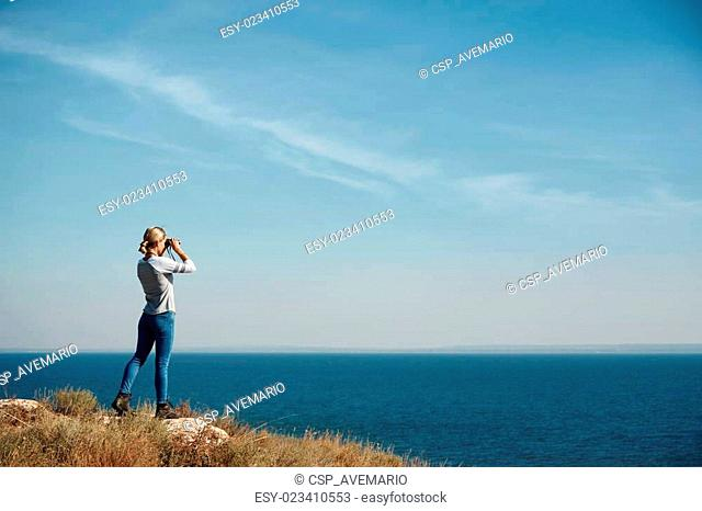 Woman tourist looking through binoculars at distant sea, enjoying landscape, copy space