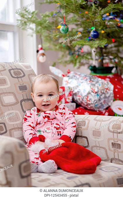 Portrait of a toddler in her festive Christmas pyjamas in front of the Christmas tree; Langford, British Columbia, Canada