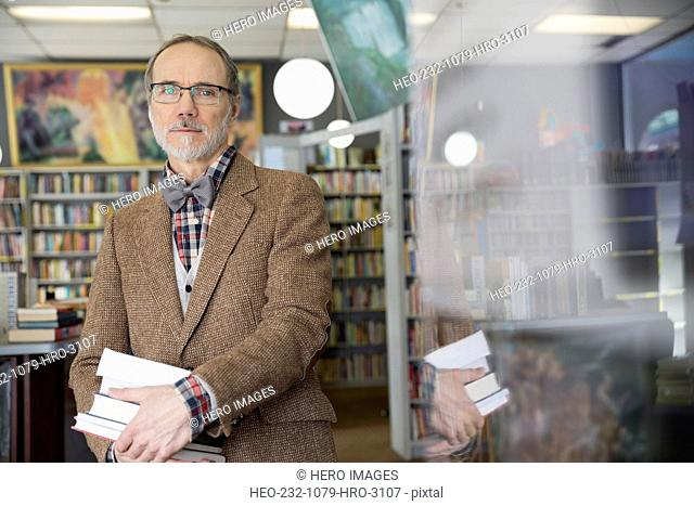 Portrait of man holding books in bookstore
