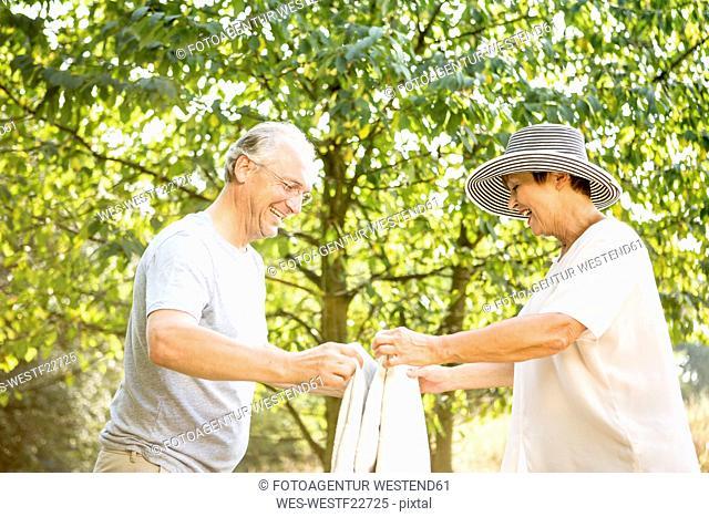 Happy senior couple folding blanket in park