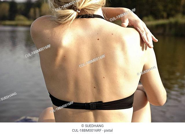 Young woman applying lotion to skin