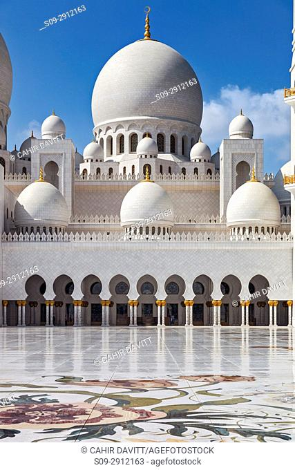 Interior courtyard of the Sheikh Zayed Grand Mosque in Abu Dhabi, with colourful inlaid marble flower motifs and main prayer hall dome, Abu Dhabi