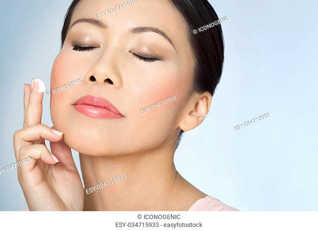 Closeup of beautiful Asian woman with glowing skin over thirty applying facial skincare cream with eyes closed
