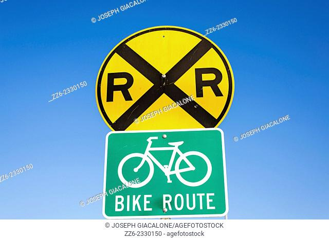 Railroad crossing warning sign, and bike route sign