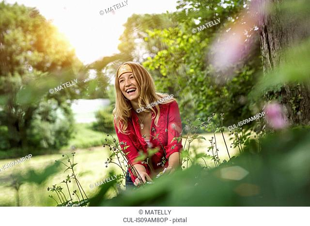 Young woman laughing whilst cutting flowers in garden