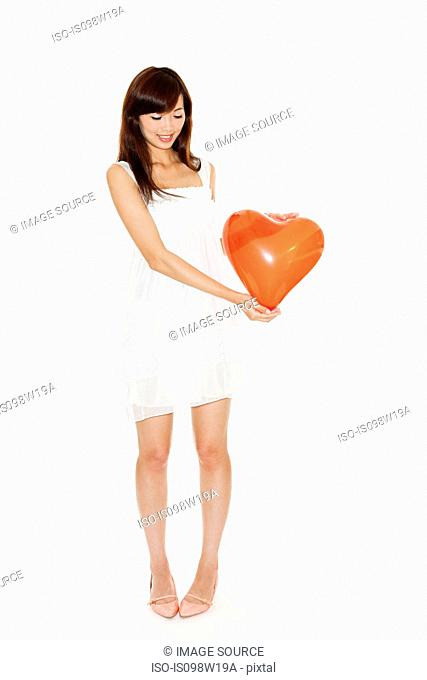 Woman holding red heart shaped balloon, studio shot