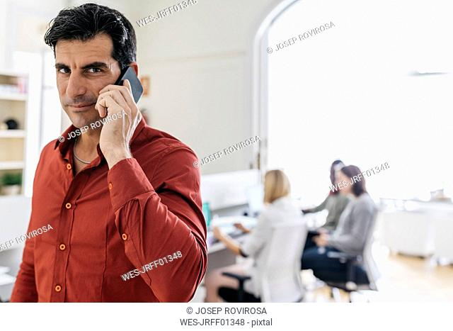 Businessman talking on the phone in office with colleagues working in background