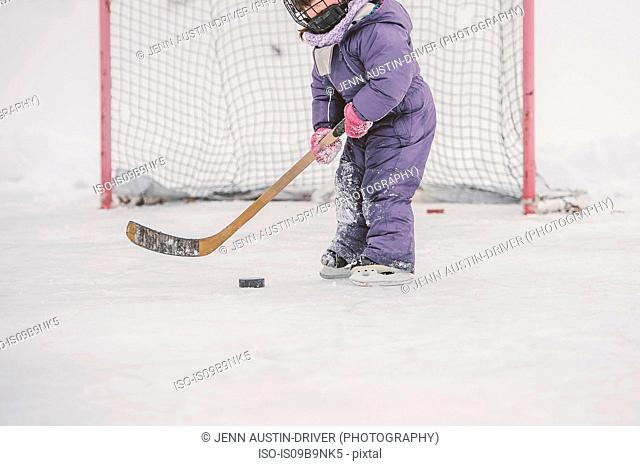 Young girl playing ice hockey, preparing to hit puck, mid section