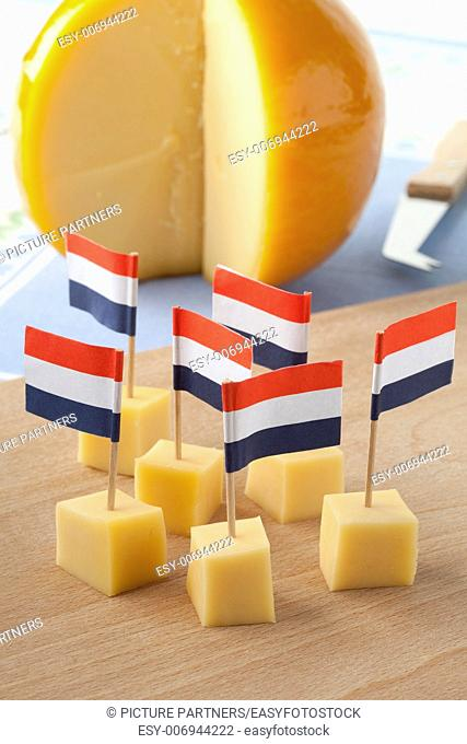 Yellow Edam cheese blocks with Dutch flags as a snack