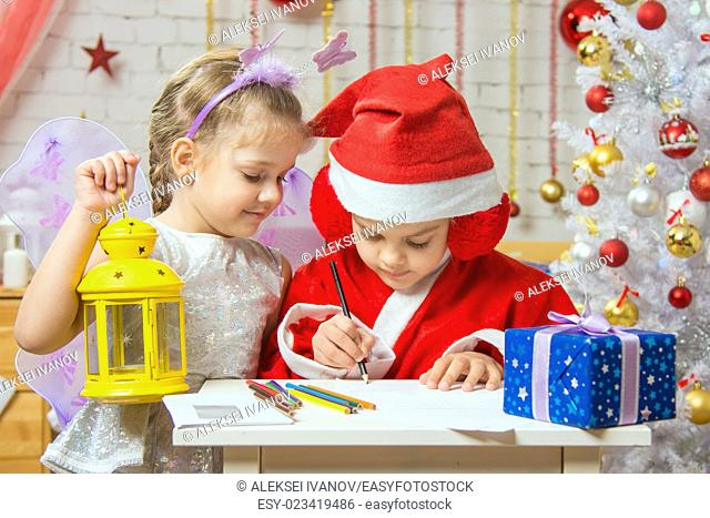 A girl dressed in a red suit Santa Claus draws pencils sitting at the table, next is a girl dressed as a fairy with the candlestick