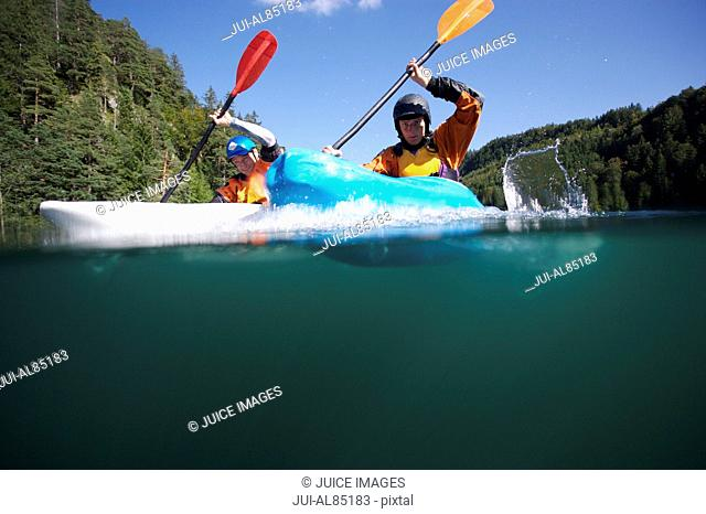 Surface shot of men paddling in kayaks