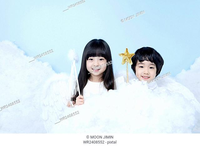 Boy and a girl with magic sticks in clouds in the background representing heaven