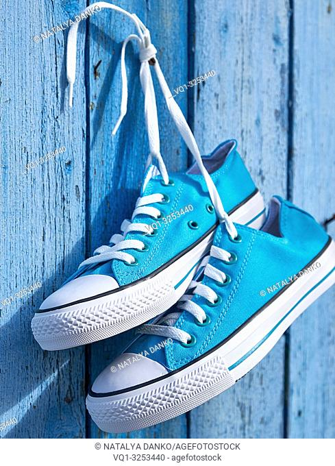 pair of blue textile sneakers hanging on a nail on the wall of old cracked wooden planks, selective focus