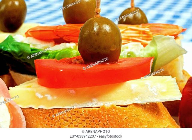 Spanish tapas selection, with Cheese and tomato topped with a green olive and served on crusty bread in the foreground, Andalusia, Spain, Western Europe