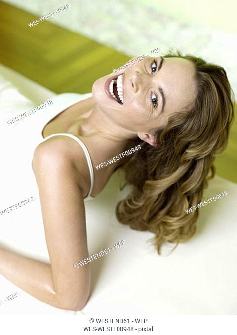 Woman lying on bed and laughing, portrait, elevated view