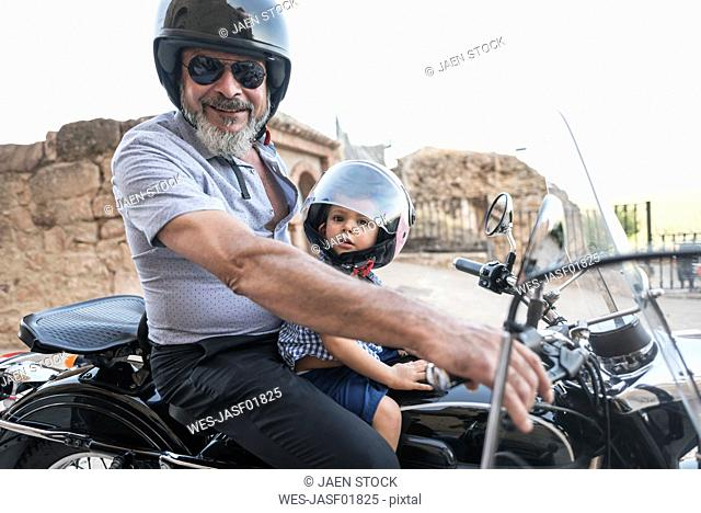 Spain, Jaen, grandfather with grandson on motorcycle with a sidecar
