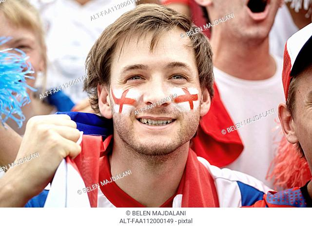British football fan smiling at match, portrait