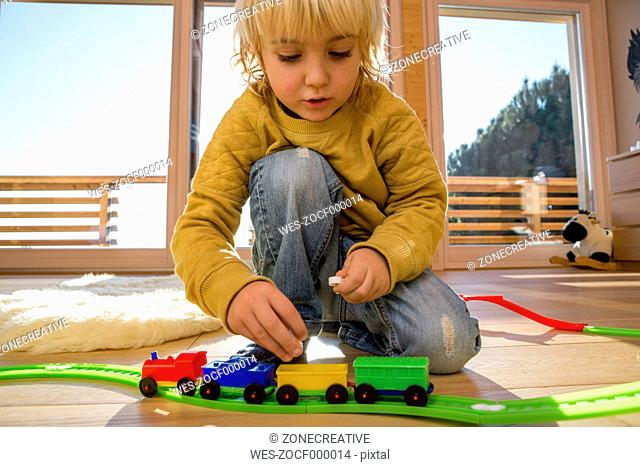 Little boy playing with toy train on the wooden floor at home