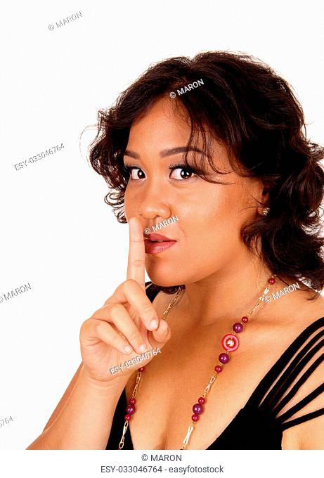 A mixed raced woman, looking into the camera holding her finger overher mouth gesturing silence, isolated for white background