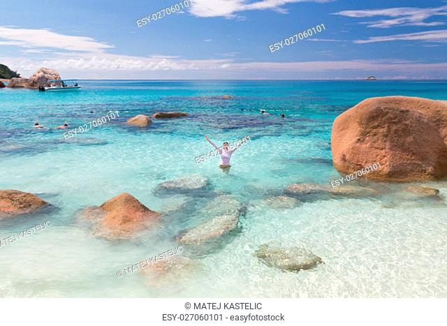 Woman arms rised wearing bikini and lycra top enjoying swimming and snorkeling at amazing Anse Lazio beach on Praslin Island, Seychelles