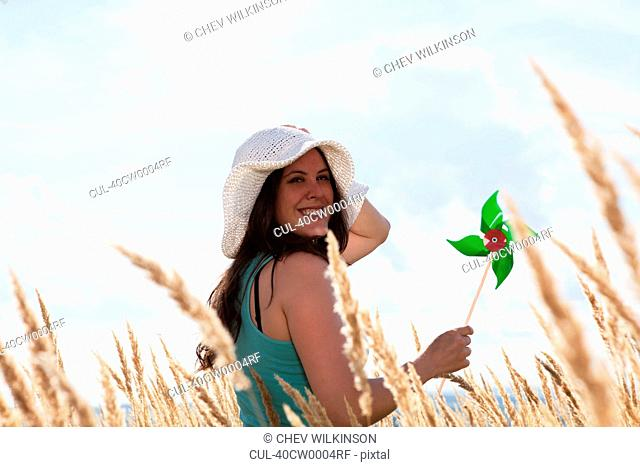 Woman holding pinwheel in wheatfield
