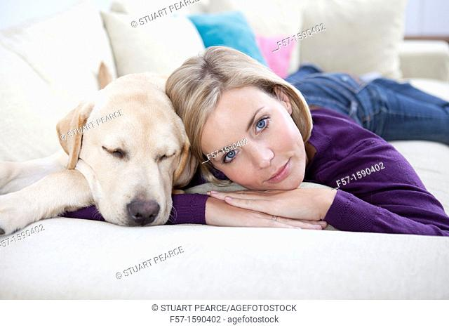 Young woman lying on a sofa with her Dog