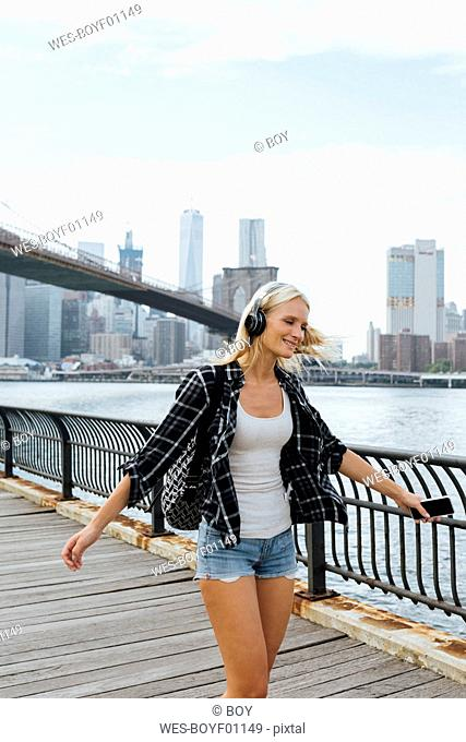 USA, New York City, Brooklyn, happy young woman with headphones and cell phone dancing at the waterfront