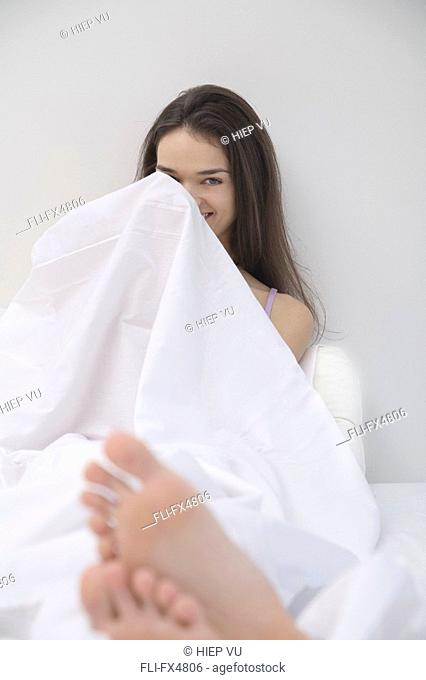 Woman Hiding behind Sheet in Bed
