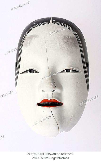 traditional but broken japanese noh theatre mask of ko-omote representing young beauty woman - symbolism of growing older