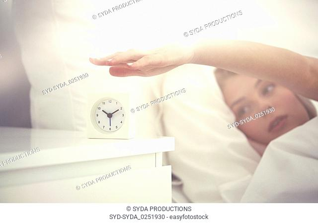 close up of woman with alarm clock in bed at home