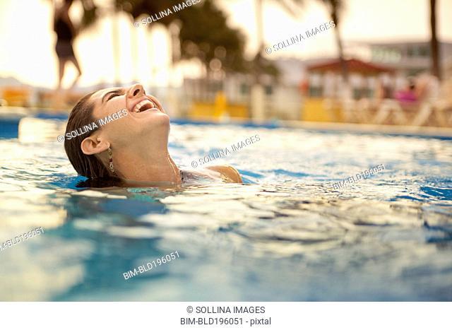 Laughing Hispanic woman swimming in swimming pool