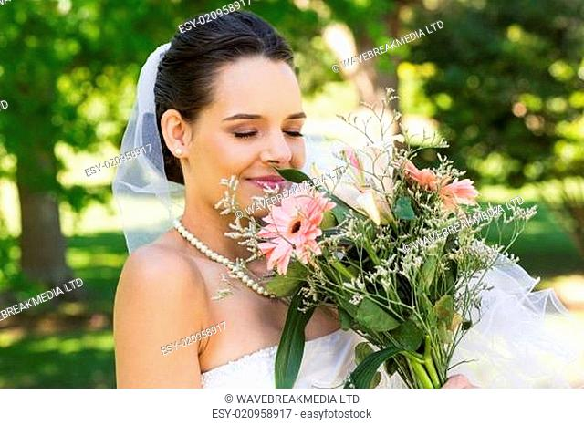 Close-up of a beautiful bride with bouquet in park