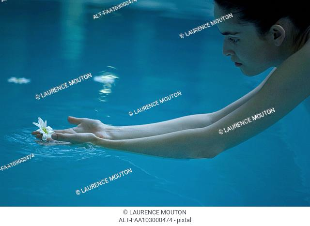 Woman reaching for flower floating in pool